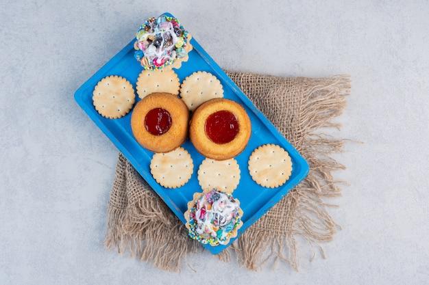 大理石のテーブルの青い大皿にクラッカー、カップケーキ、ゼリーを詰めたケーキ。