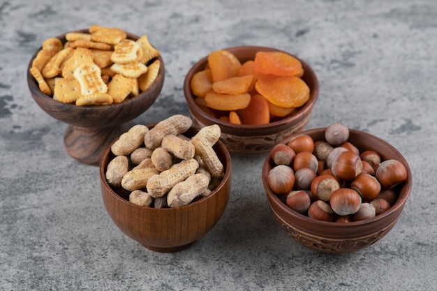 Crackers, dried apricots, hazelnuts and peanuts in wooden bowls.
