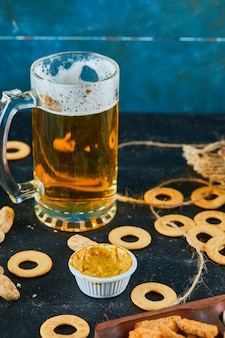 Crackers and a glass of beer on dark surface.