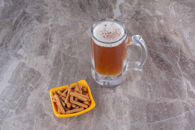 Crackers and glass of cold beer on marble surface. high quality photo