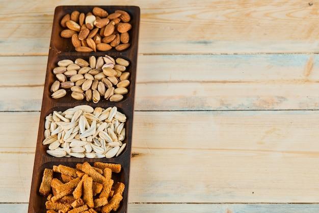 Crackers, pistacchi e mandorle sul piatto di legno.