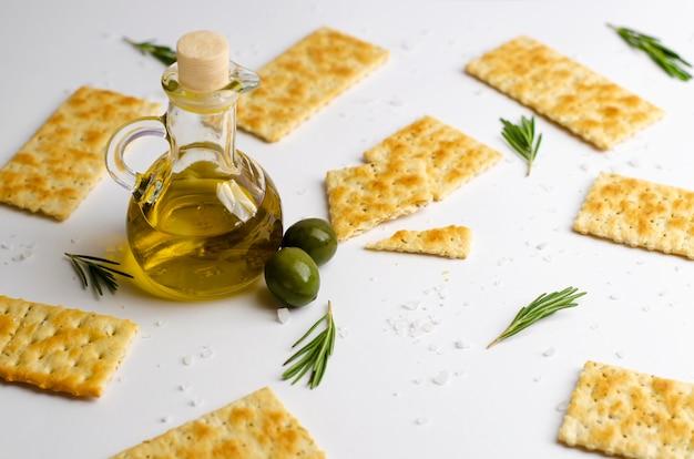 Crackers, rosemary herb, olives, salt and olive oil on white
