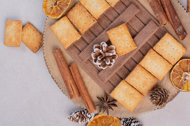Crackers with aroma cinnamon sticks on wooden plate . high quality photo