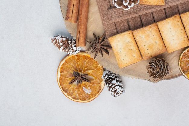 Cracker con bastoncini di cannella aroma sul piatto di legno. foto di alta qualità