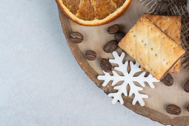 Крекеры с ароматными кофейными зернами на деревянной тарелке. фото высокого качества