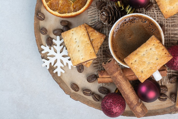 Crackers with aroma cup of coffee on wooden plate . high quality photo