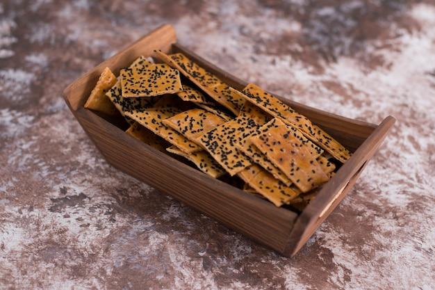 大理石の木製トレイに黒いクミンが付いたクラッカー。
