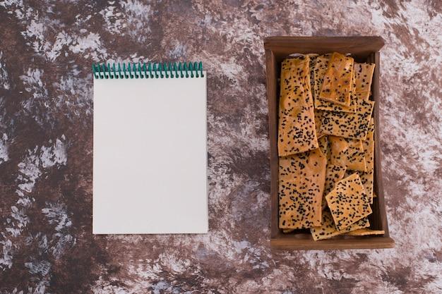 ノートブックを脇に置いた木製トレイに黒いクミンが入ったクラッカー。