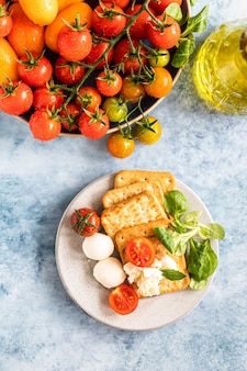 Crackers with cherry tomatoes salad and mozzarella