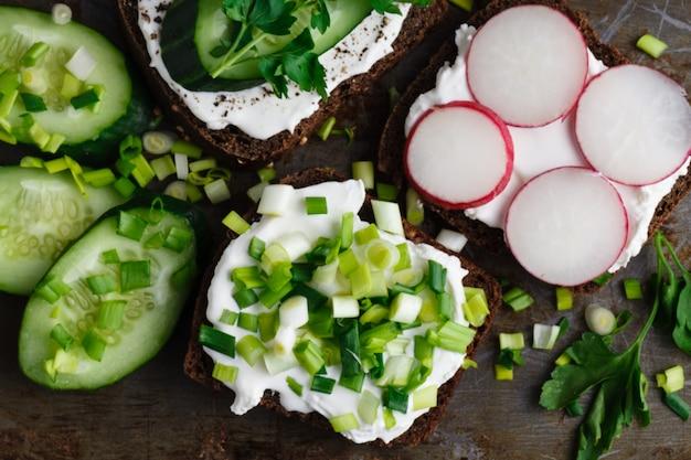 カッテージチーズ、大根、クレソンのサラダと新鮮なハーブで飾られたキュウリのクラッカー