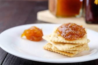 Crackers with orange jam on wooden background