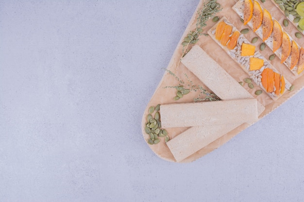 Crackers with sliced fruits and pumpkin seeds