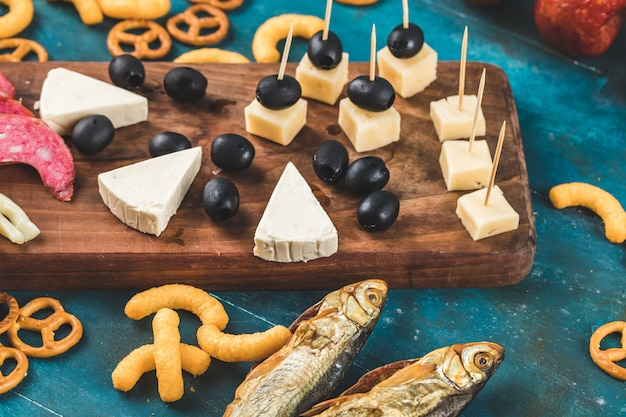 Crackers with smoked fish and cheese on blue background
