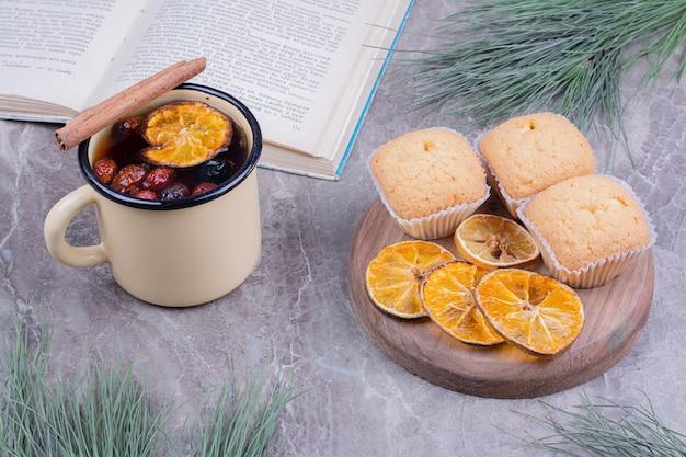 Cracker su una tavola di legno con fettine di limone e una tazza di glintwine