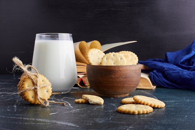 Crackers in a wooden cup with a glass of milk.