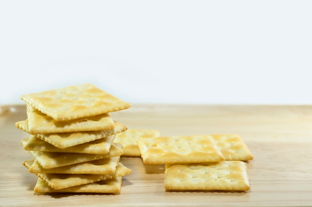 Crackers on wooden dish and white background.