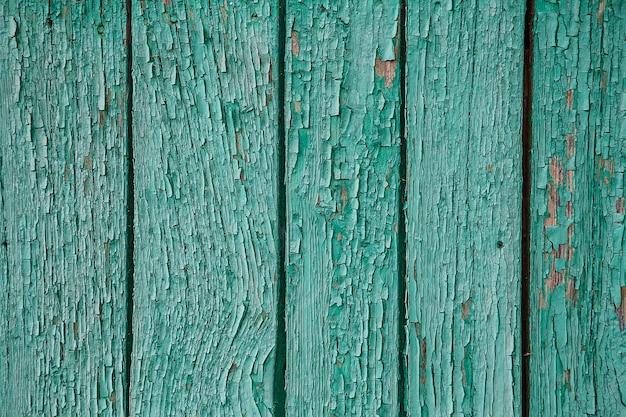 벽에 파란색 페인트를 크래킹하고 필링합니다. 녹색 필 링 페인트와 빈티지 나무 배경입니다. 조사 된 페인트로 오래 된 보드