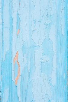 벽에 파란색 페인트를 크래킹하고 필링합니다. 필 링 페인트와 빈티지 나무 배경입니다. 조사 된 페인트로 오래 된 보드