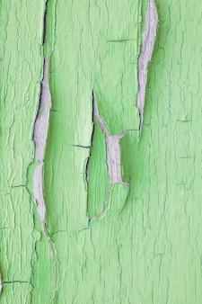 벽에 녹색 페인트를 부수고 박리. 필 링 페인트와 빈티지 나무 배경입니다. 조사 된 페인트로 오래 된 보드