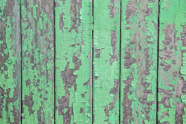 壁の緑色のペンキのひび割れと剥離