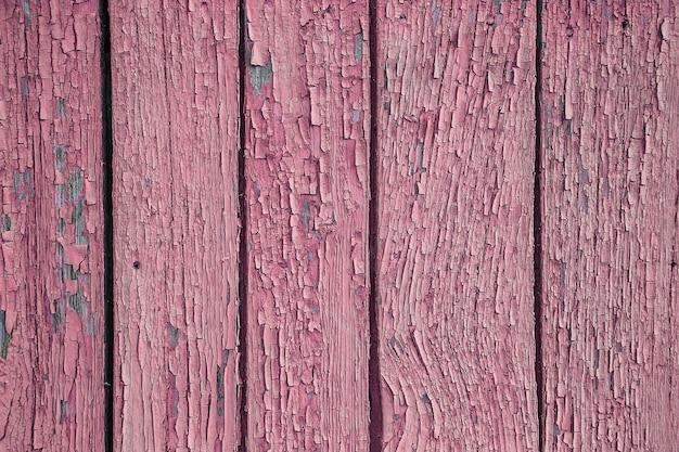 벽에 분홍색 페인트를 부수고 박리. 녹색 필 링 페인트와 빈티지 나무 배경입니다. 조사 된 페인트로 오래 된 보드