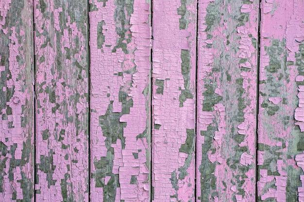 壁のピンクのペンキのひび割れと剥がれ