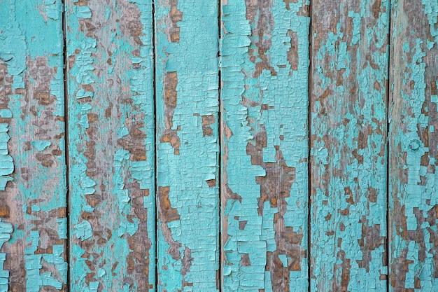 벽에 청록색 페인트를 부수고 박리. 블루 필 링 페인트와 빈티지 나무 배경입니다. 조사 된 페인트로 오래 된 보드