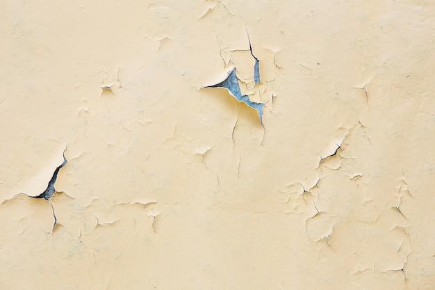벽에 노란색 페인트를 부수고 벗겨냅니다. 필 링 페인트와 빈티지 나무 배경입니다. 조사 된 페인트로 오래 된 보드