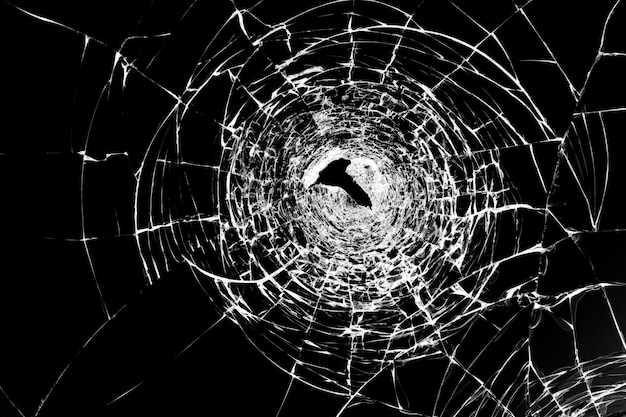 Cracks on broken glass after gun shots. punched hole in windshield vandalism and assault with a firearm. damaged window robbers.