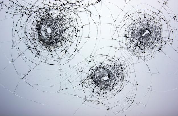 Cracks on broken glass after gun shots. vandalism and assault with a firearm. damaged window robbers.
