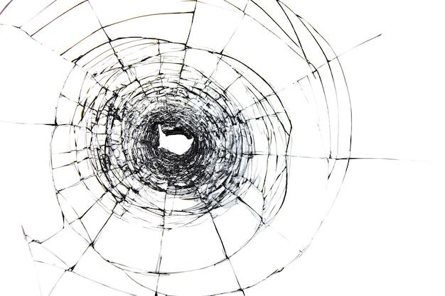 Cracks on glass from shot, broken glass on white