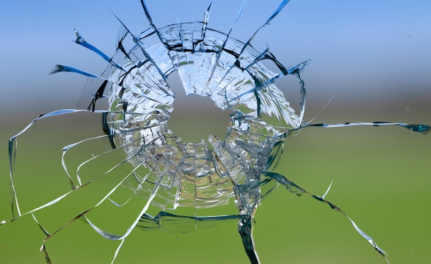Cracks in the glass, a hole from a bullet in the window