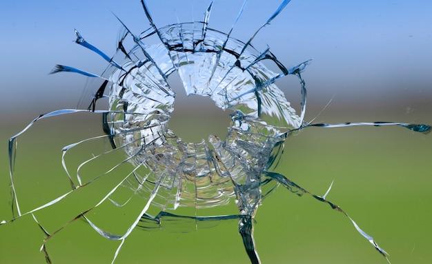 Трещины в стекле, дыра от пули в окне