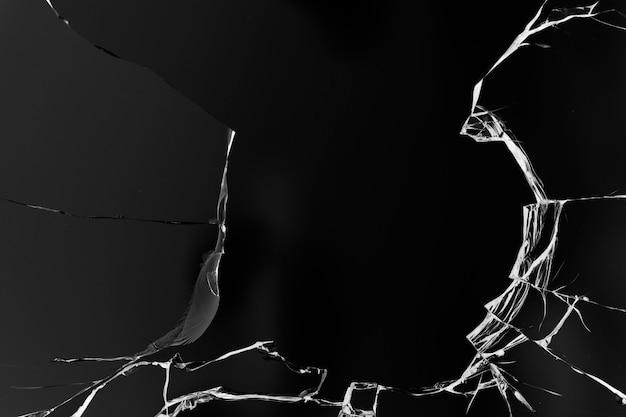 검은 색 표면에 총알 구멍이있는 유리의 균열
