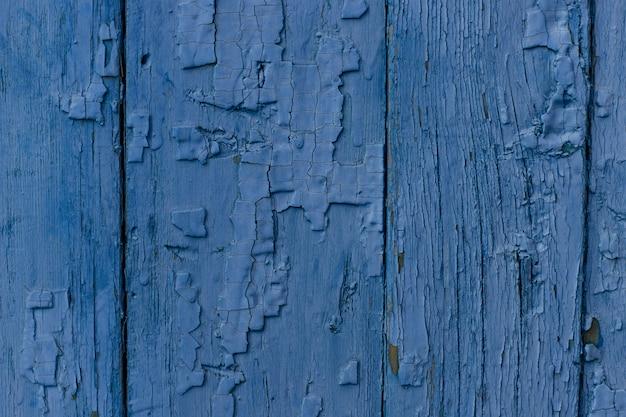 Трещины старой синей краской на деревянной доске. классический синий старинный фон.