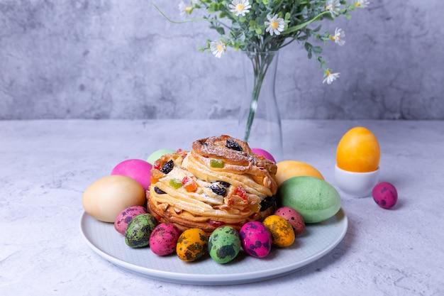 Краффин (cruffin) с изюмом, орехами и цукатами. хлеб пасхальный кулич и крашеные яйца. пасха. крупный план.