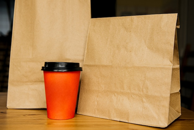 Craft bag with food and a paper cup with coffee or tea. takeaway food concept