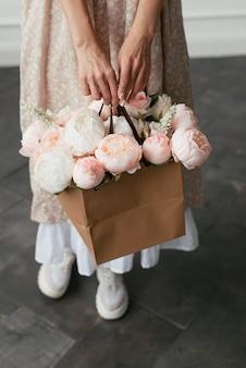 白ピンクの牡丹を手にしたクラフトバッグ
