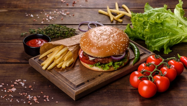 검은 배경에 수제 쇠고기 버거와 감자 튀김 프리미엄 사진