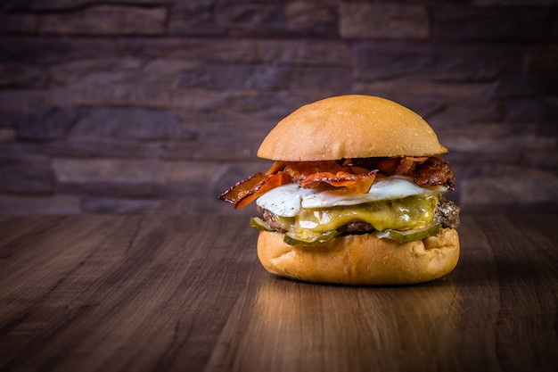 Craft beef burger with cheese, egg, bacon and pickles on wood table