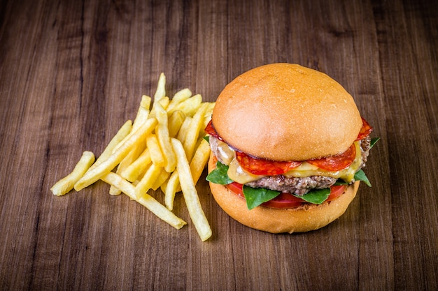 Craft beef burger with cheese, italian peperoni, tomato, basil leafs and french fries on wood table