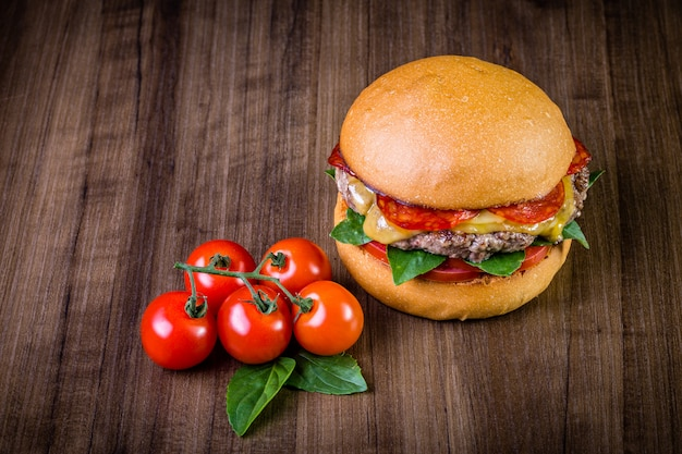 Craft beef burger with cheese, italian peperoni, tomato and basil leafs on wood table