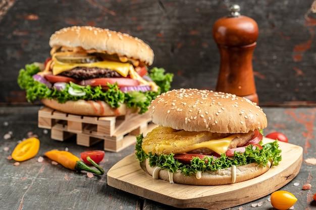素朴な木製の背景に野菜を使ったクラフトビーフバーガー。ファーストフードとジャンクフードのコンセプト