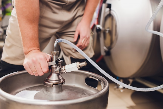 Craft beer brewing equipment in brewery metal tanks, alcoholic drink production.