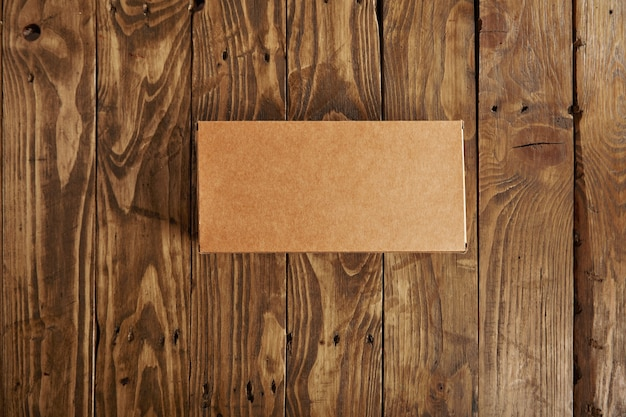 Craft blank cardboard package box presented on stressed brushed wooden table, top view