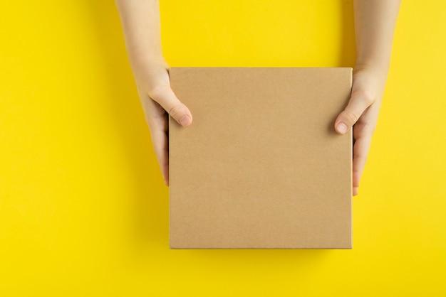 黄色の背景、上面図に手でクラフトボックス。スペースをコピーします。モックアップ。