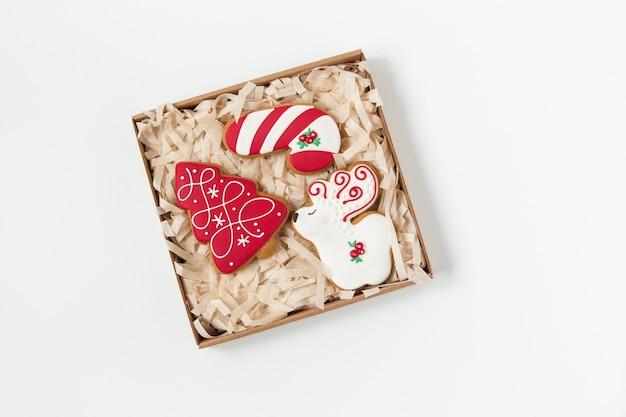 クリスマスジンジャーブレッドクッキーのクラフトボックス。木の形と鹿。上面図。白色の背景。ミニマリストスタイル。