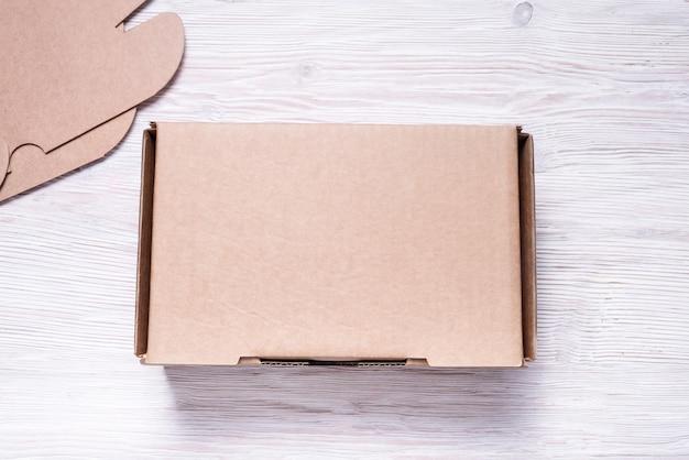 나무 배경에 갈색 판지 상자 공예