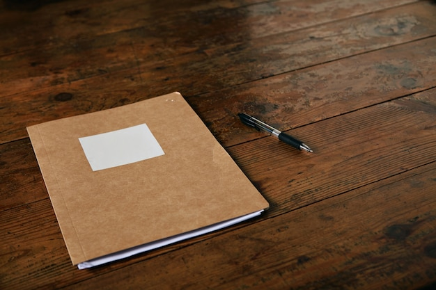 Craft brown folder with empty white label and a ballpoint pen on a rustic dark brown table