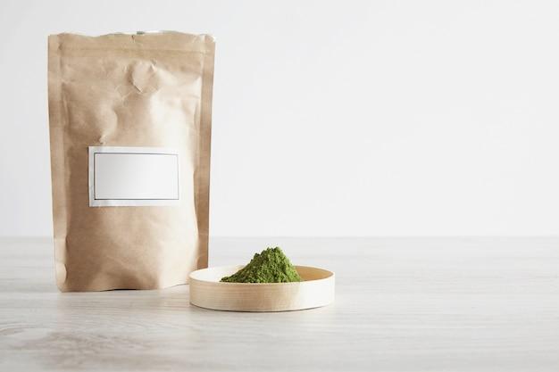 シンプルな背景で隔離の白い木製のテーブルのボックスに茶色の紙袋とプレミアム有機抹茶茶粉を作ります。準備、販売プレゼンテーションの準備ができました。